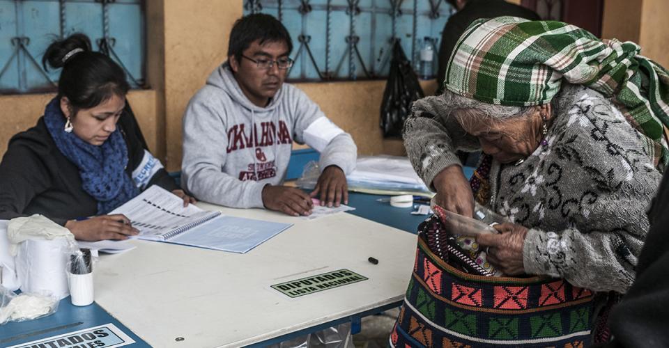 Una anciana busca su DPI para poder ejercer su voto.