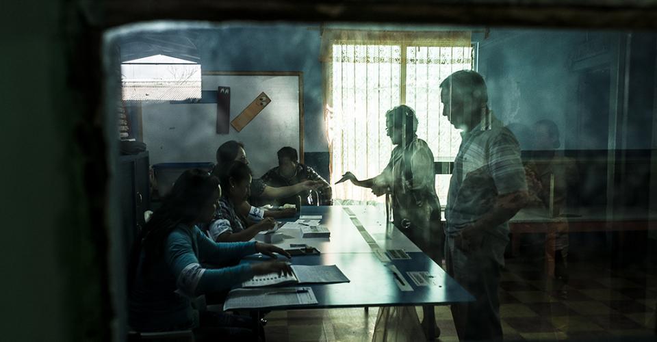 Una mujer recibe su papeleta en una mesa electoral de Chimaltenango.