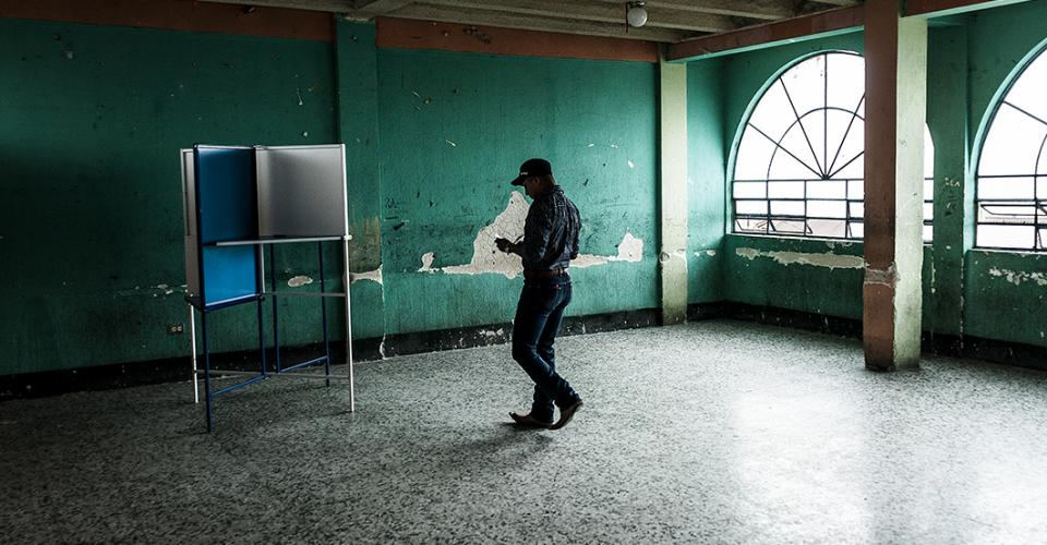 Un hombre vota en uno de los vacíos salones del centro de votación de Zaragoza de Heredia.