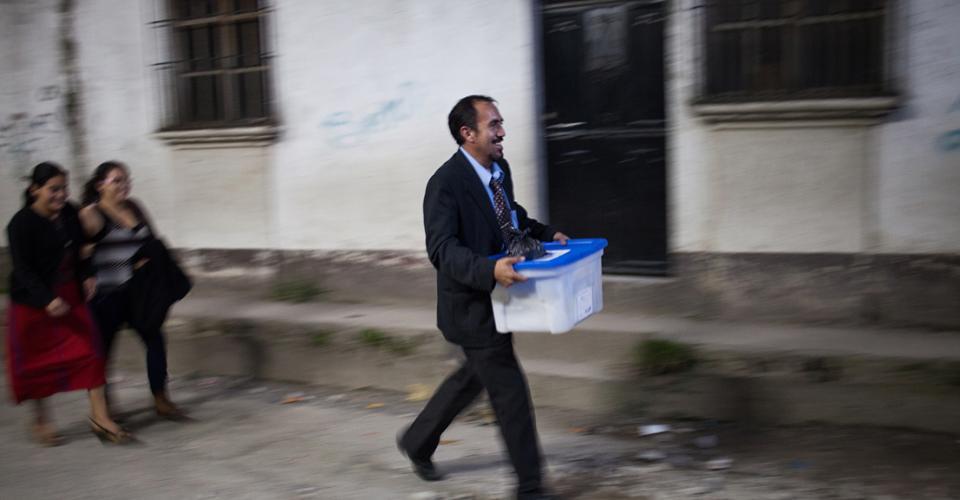 Miembros de un centro de votación de Nebaj, El Quiché, llevan los resultados finales de una mesa por las calles del casco urbano rumbo al salón municipal.