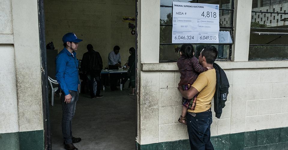 Una niña observa curiosa el momento en que su madre deposita el voto en un centro de votación de Chimaltenango.