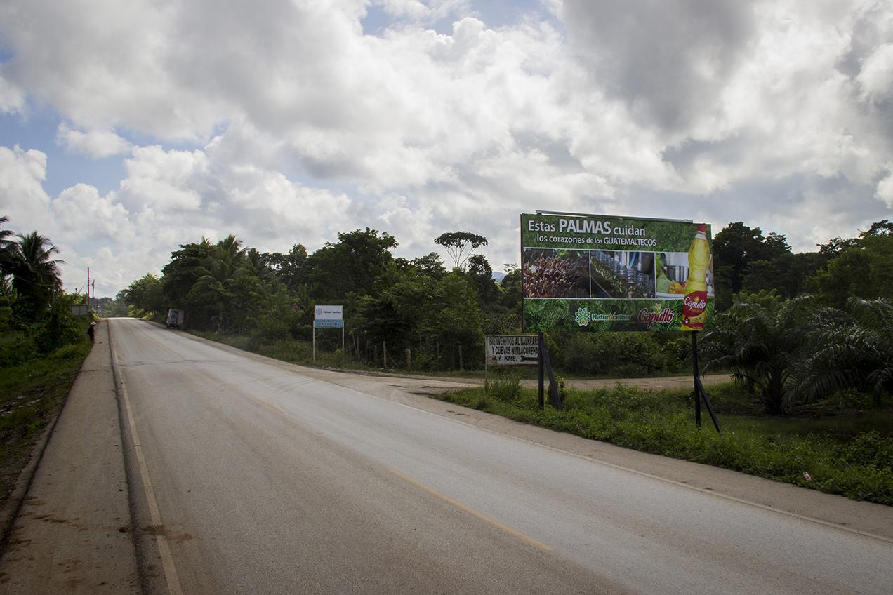 """Sobre la franja transversal, en las afueras de la planta extractora, NaturAceites se anuncia: """"cuidando los corazones de los guatemaltecos""""."""