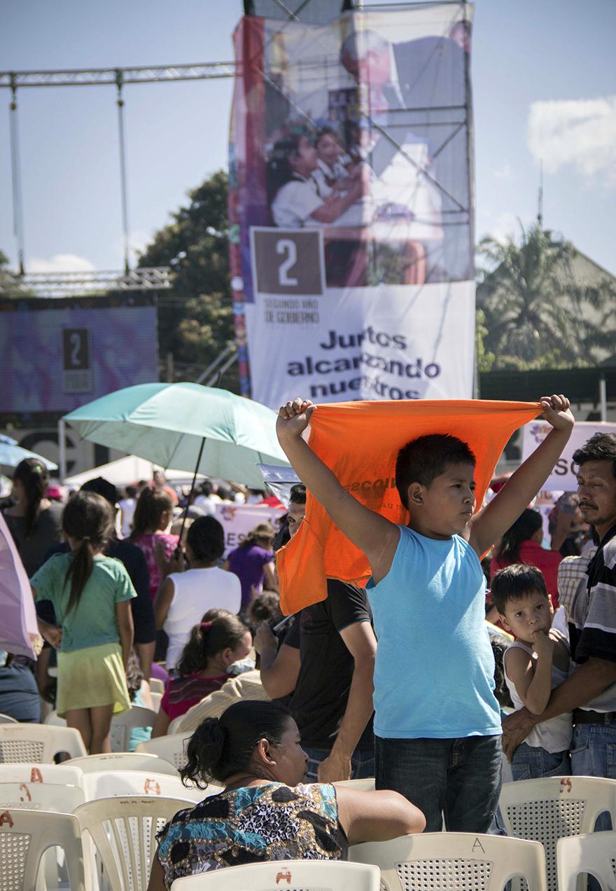 El sol golpeó al público que llegó a Escuintla. Un niño se cubre con una camisa naranja, color que resaltaba entre los espectadores.