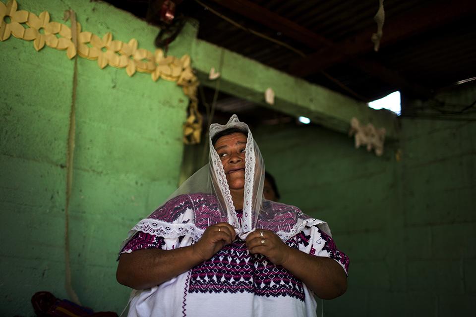 María Alberta Choc, enseña un traje ceremonial usado por las mujeres durante las procesiones de la cofradía local.