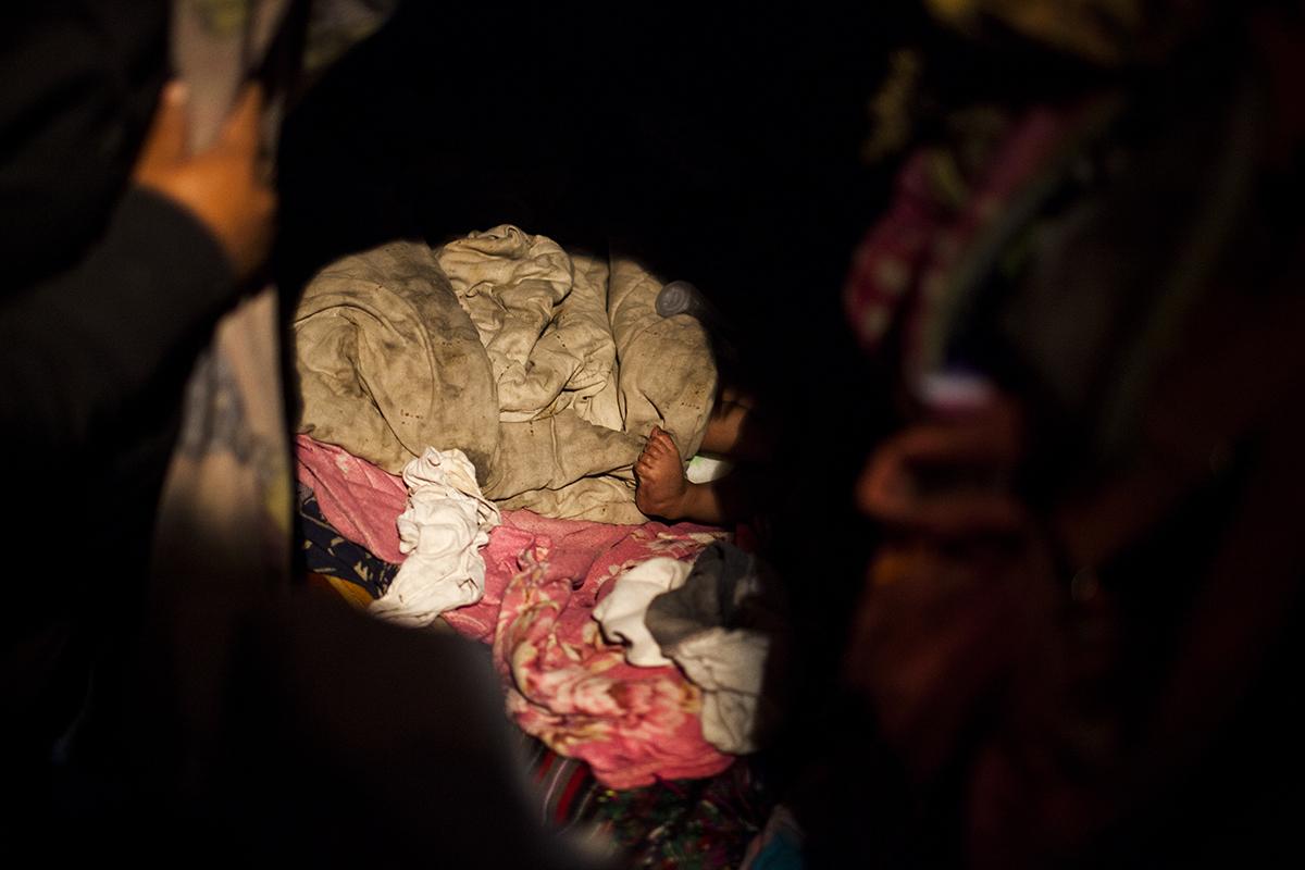 El pie de José Isaías, de un año y 8 meses, emerge de la cama, en la madrugada. Vive junto con su mamá y hermanas en el asentamiento Manuel Colom Argueta.