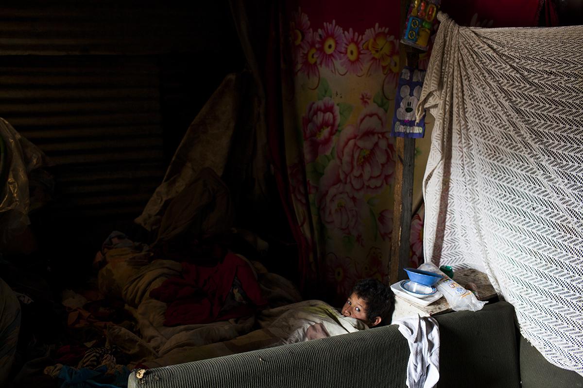 Jerson, 11, se asoma desde el sofá donde suele dormir, en una casa del asentamiento Manuel Colom Argueta.