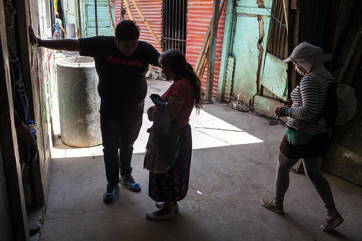 El pastor Carlos Galindo, 33, confiesa a una anciana en la entrada del asentamiento Manuel Colom Argueta. El religioso inauguró un proyecto de ayuda humanitaria y acompañamiento espiritual a niños y adolescentes en noviembre de 2013, denominado Pan de Vida.