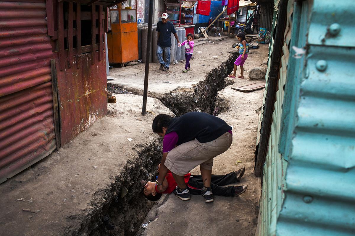 Dos niños juegan encima de la obra de reestructuración del canal de desagüe en el asentamiento Manuel Colom Argueta.