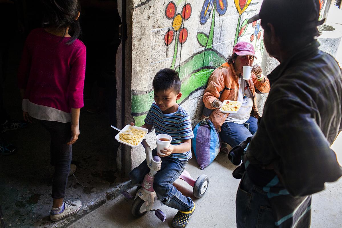 Un niño recibe un plato de pasta como parte del programa de entrega de alimentos, que el proyecto Pan de Vida promueve a beneficio de niños y necesitados del asentamiento Manuel Colom Argueta.