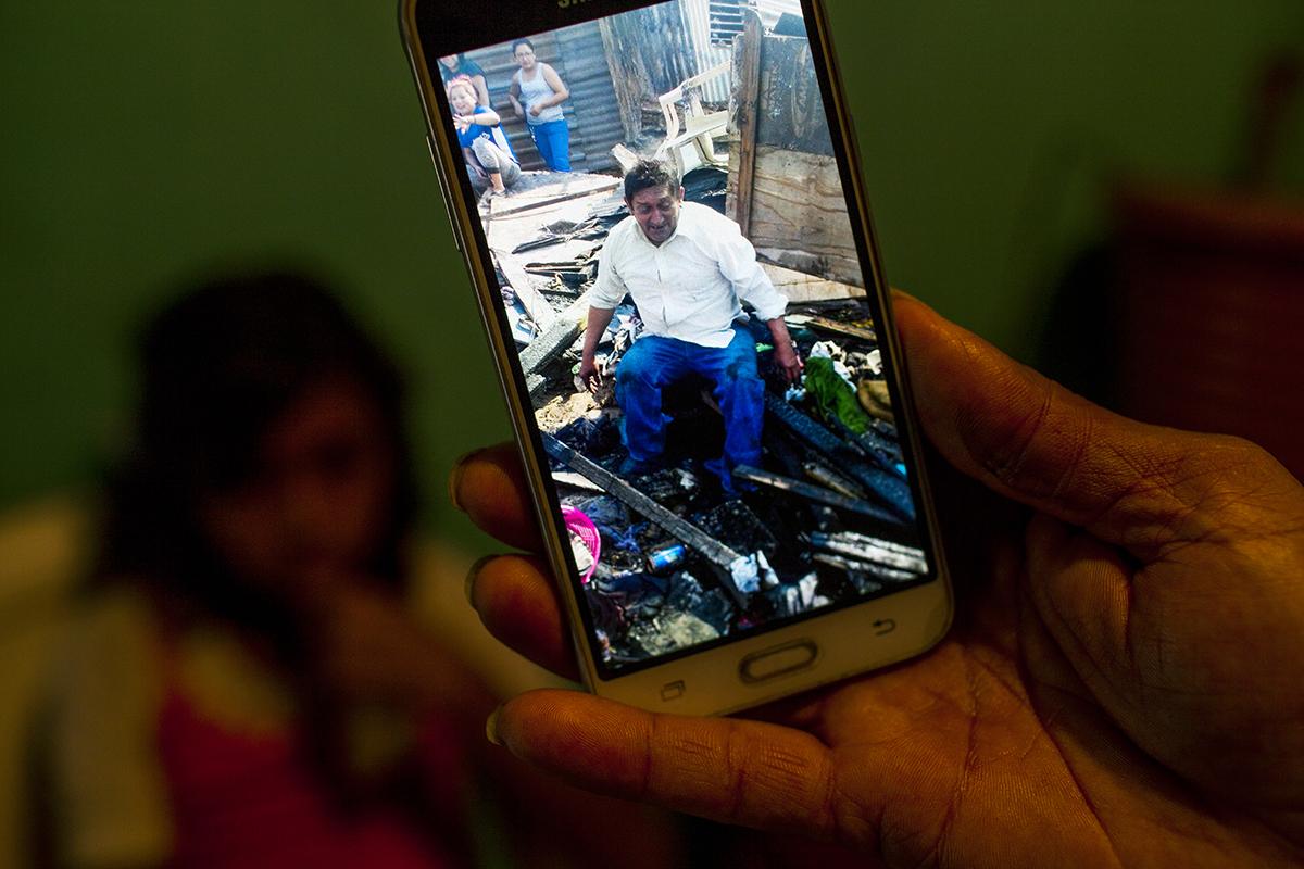 El hijo de Eduardo Sánchez Sinay, 64, enseña la foto del padre encima de los restos de su casa, la mañana siguiente del incendio del 14 de febrero que destruyó la vivienda del anciano.