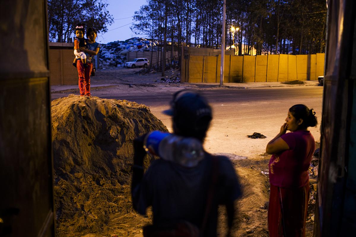 Al atardecer, Juana Chávez, 26, originaria de Nebaj y madre de 4 hijos, espera a su esposo de regreso del relleno sanitario, en la entrada del asentamiento Manuel Colom Argueta.