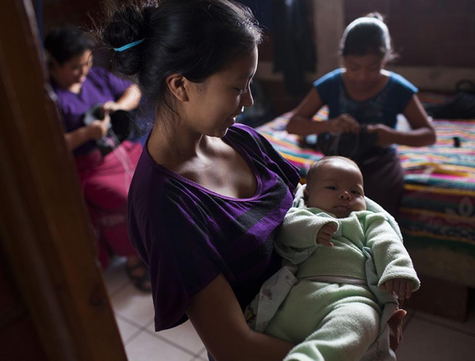 Vilma, de 17 años, muestra a su hijo Esdran de 3 meses. Detrás de ella, doña Maximiliana, viuda desde el 2009 y mamá de Vilma, cose zapatos junto con su hija menor Andrea, de 12 años.