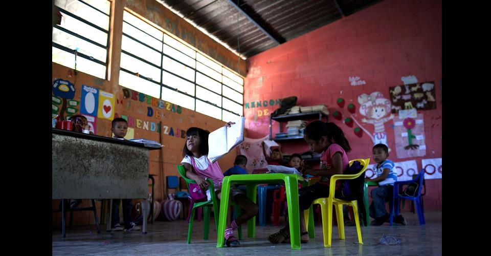 Mayra Amador enseña su cuaderno a la maestra en el aula de preprimaria, junto con sus compañeros de clase. Para equipar el aula, los padres de los niños colaboraron económicamente en la compra de las sillas