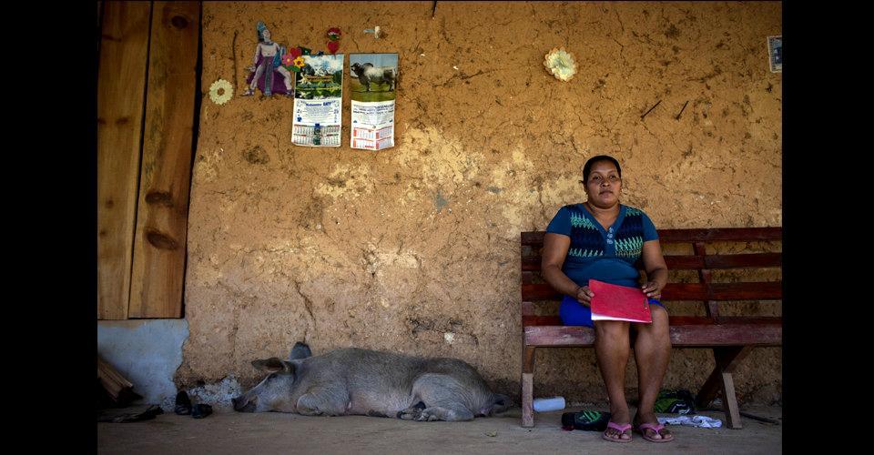 Angelina Raymundo Vásquez, 35 años, mamá de Mayra, posa enfrente de su casa con la copia de la sentencia que salvó la vida de su hija