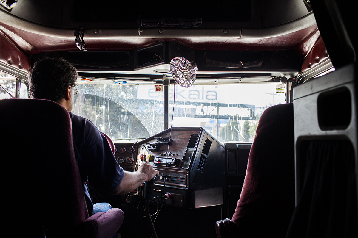 En la cabina de conducción, un piloto de tráiler maneja en el tráfico de la calzada Roosevelt rumbo a Chimaltenango.