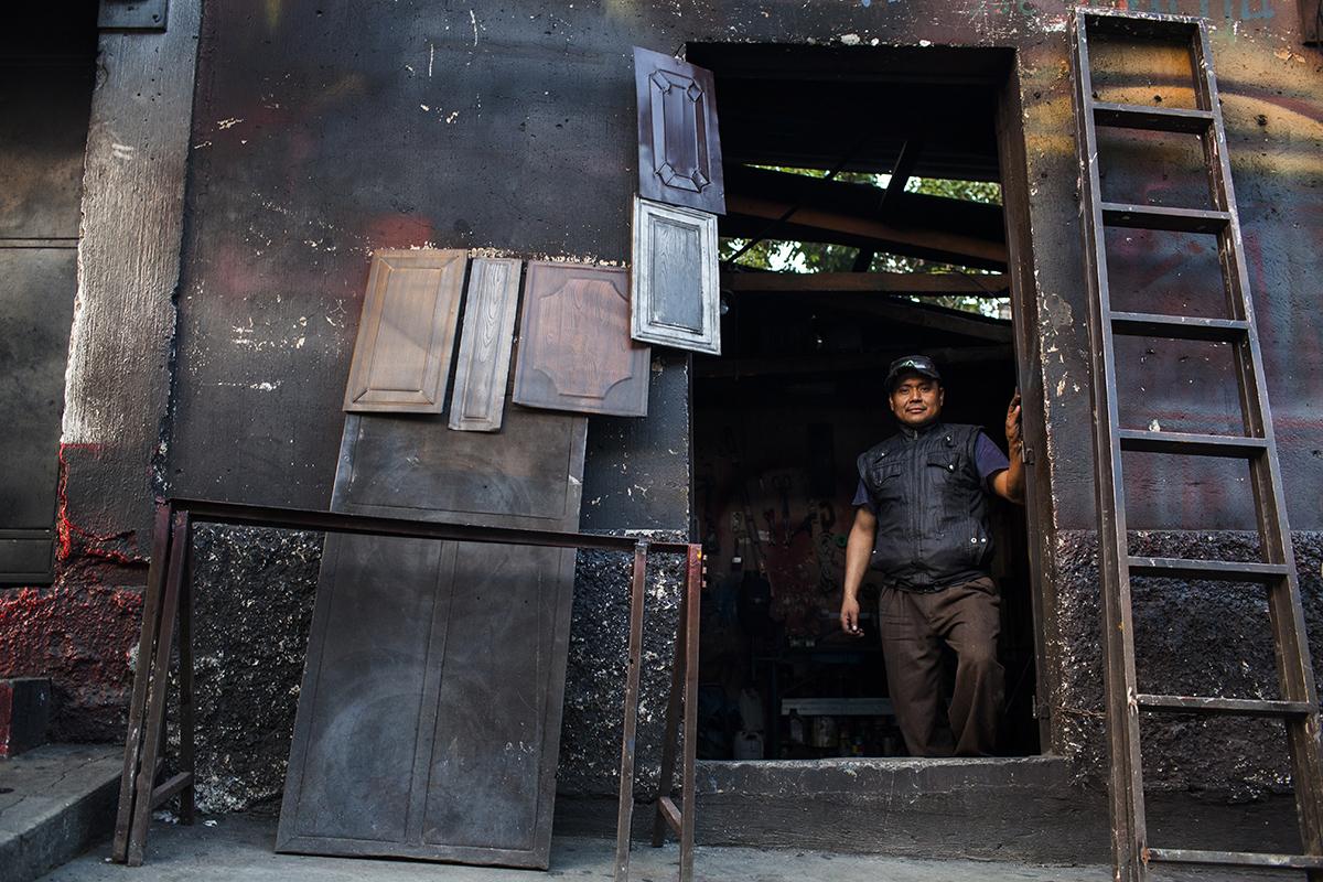 Rigoberto Sinaj en la puerta de su tienda de herrería, bajo el paso a desnivel.