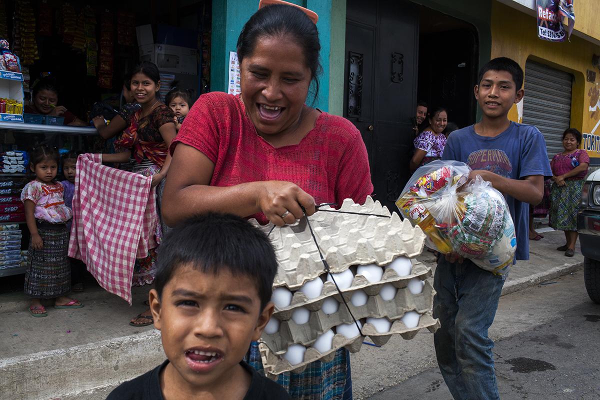 Una familia beneficiaria del programa social frente a una de las tiendas autorizadas para la venta de los alimentos