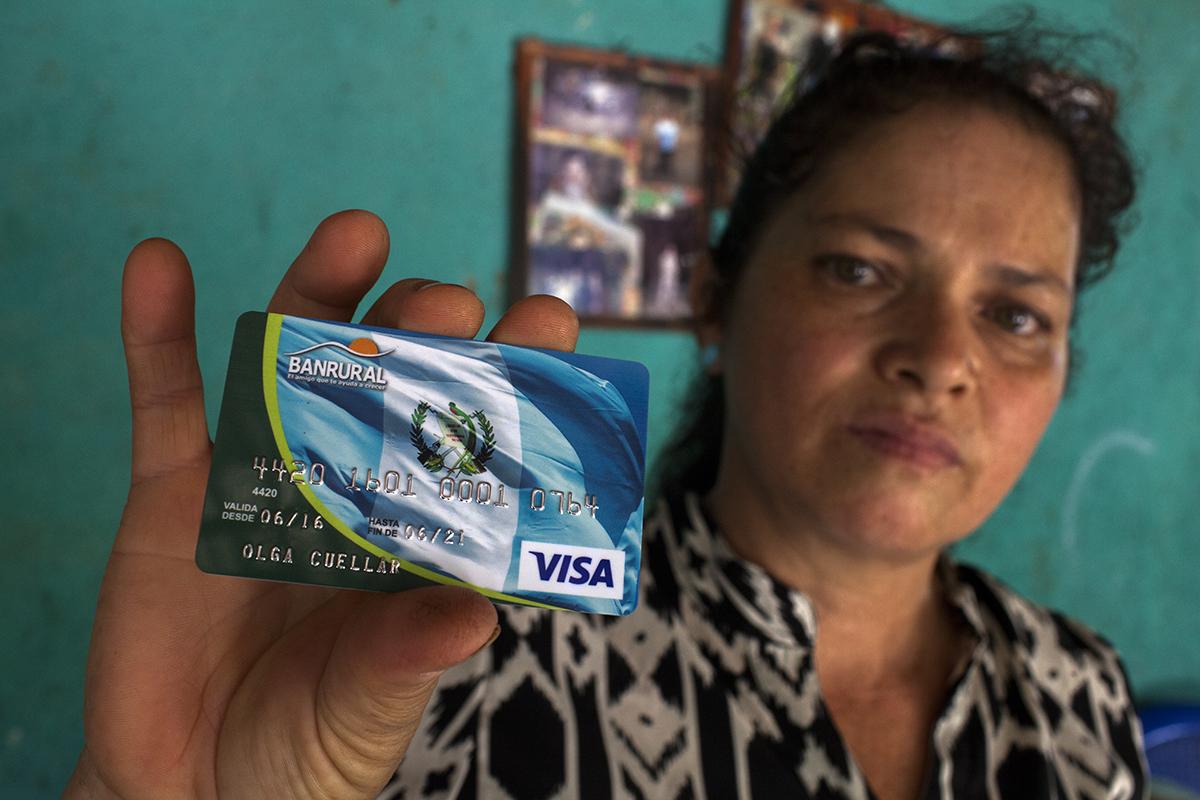Olga Cuellar, 48, muestra la tarjeta de Banrural con la cual acaba de realizar la compra financiada por el gobierno.