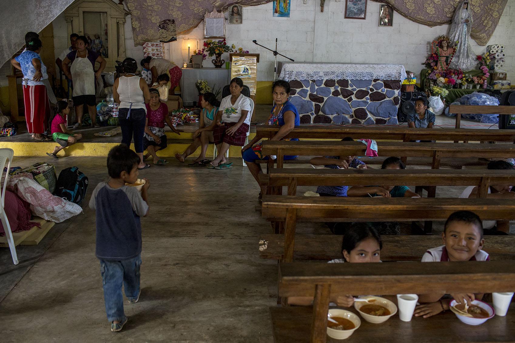 Unas familias almuerzan en la iglesia de la comunidad.