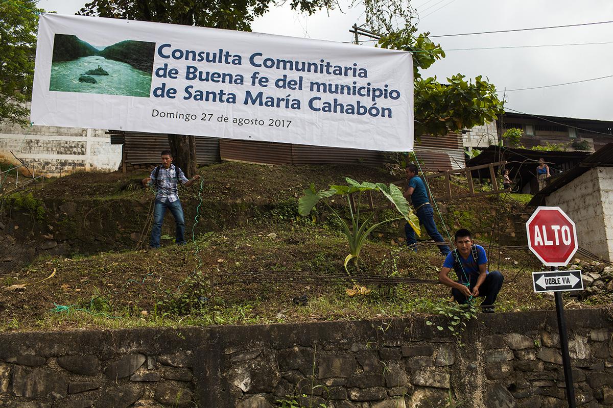 Unos voluntarios levantan una pancarta para promover la consulta comunitaria en Santa María Cahabón.