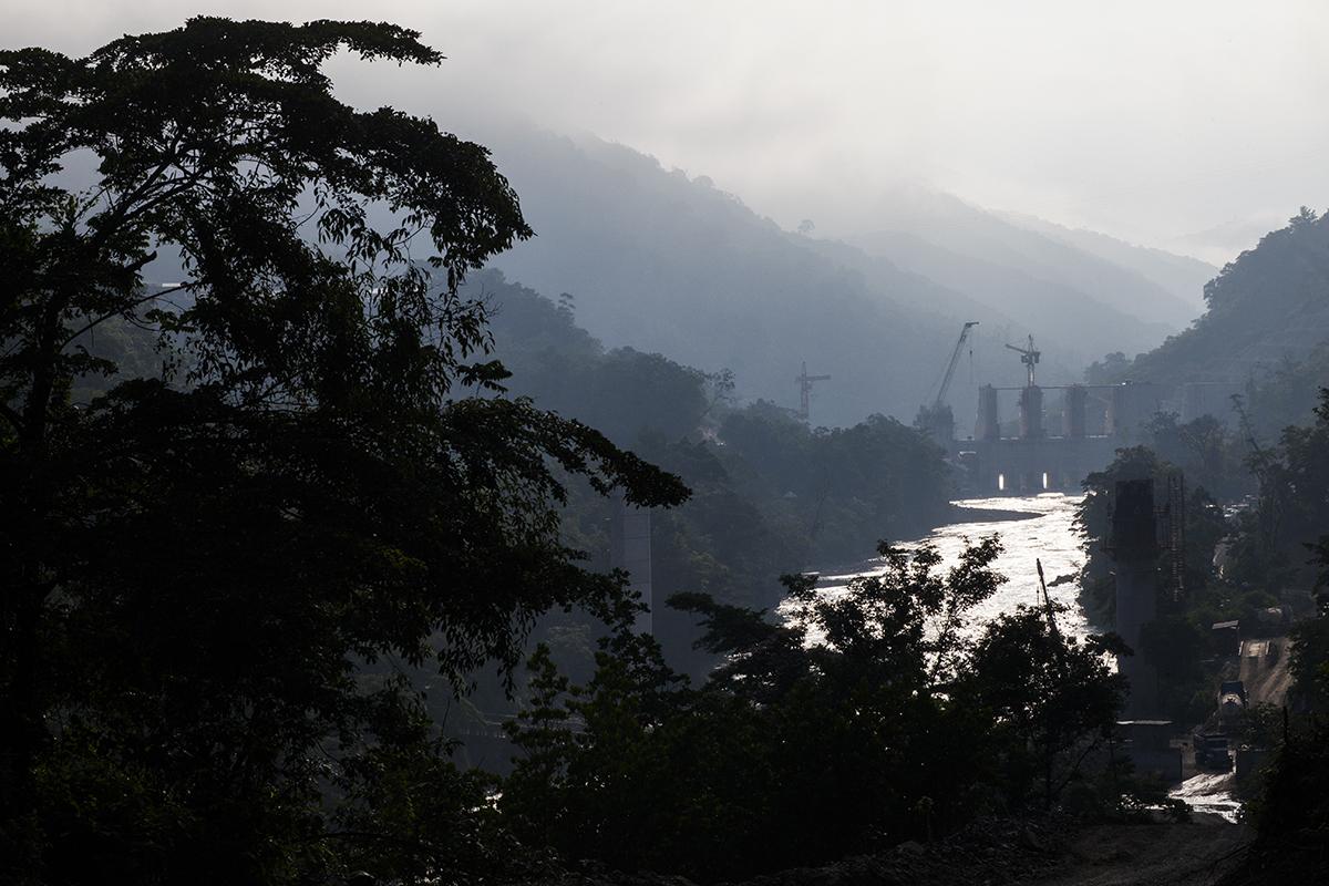 En la madrugada, las aguas del río Oxec reflejan las primeras luces del sol, pasando entre la infraestructura en construcción del proyecto hidroeléctrico Oxec 2