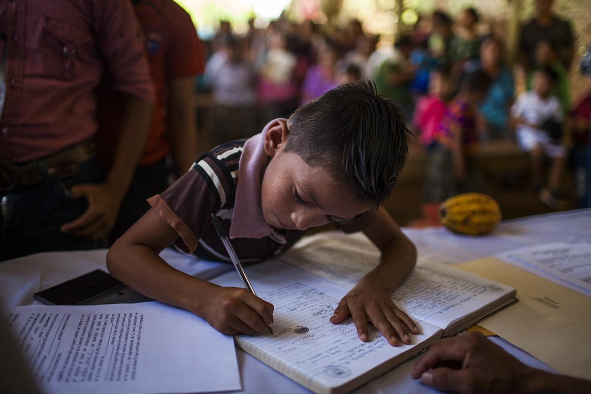 Un niño firma el acta