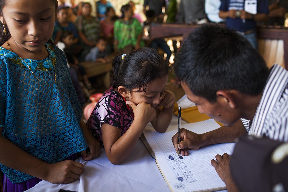 Una niña observa al responsable comunitario escribir su nombre alrededor de la huella recién puesta en el acta
