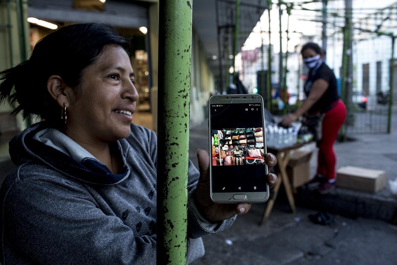Noemí Díaz, 39, también originaria de El paraíso 2, zona 18, prima de Maribel. Enseña, en una foto del celular, su puesto de venta de bolsos. Ahora, ella también se dedica a vender mascarillas y gel antibacterial. Simone Dalmasso