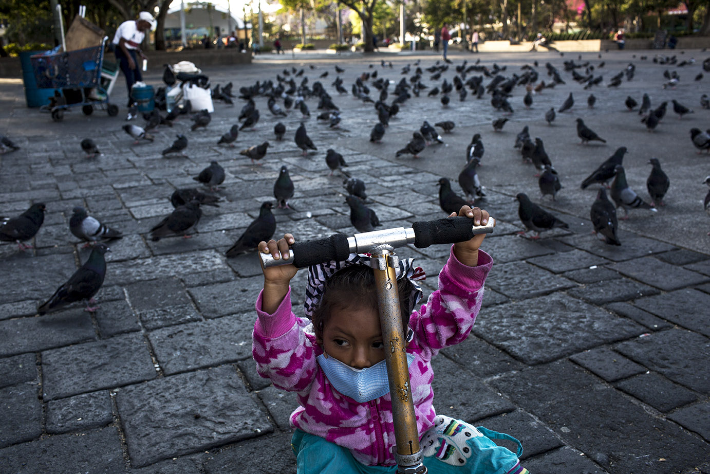 Guadalupe Gallardo, de dos años y medio, juega con su monopatín, en la plaza desierta del Parque Central de Guatemala. Sus padres son vendedores ambulantes y no pueden quedarse en casa por falta de recursos económicos. Simone Dalmasso