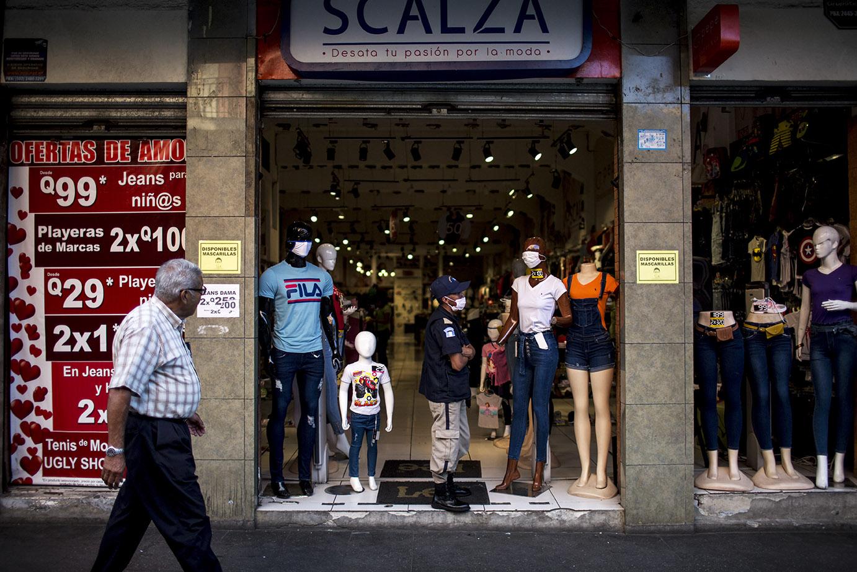 Un policía privado custodia una tienda vacía de la sexta avenida de la zona 1. Frente a la falta de personas transitando por el centro, ha aumentado el número de robos callejeros. Simone Dalmasso