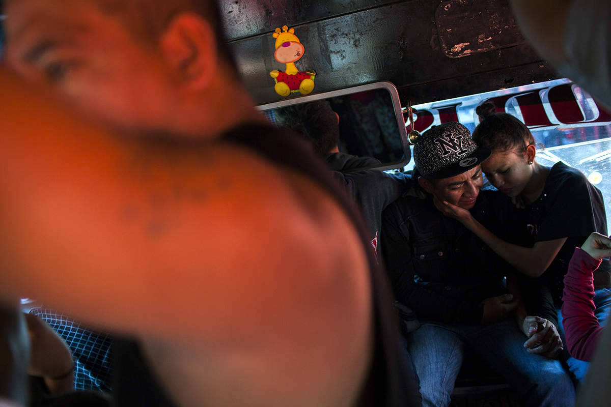 Cesar, 17, llora la muerte de su hermano en una de las camionetas que acompañan al difunto al cementerio