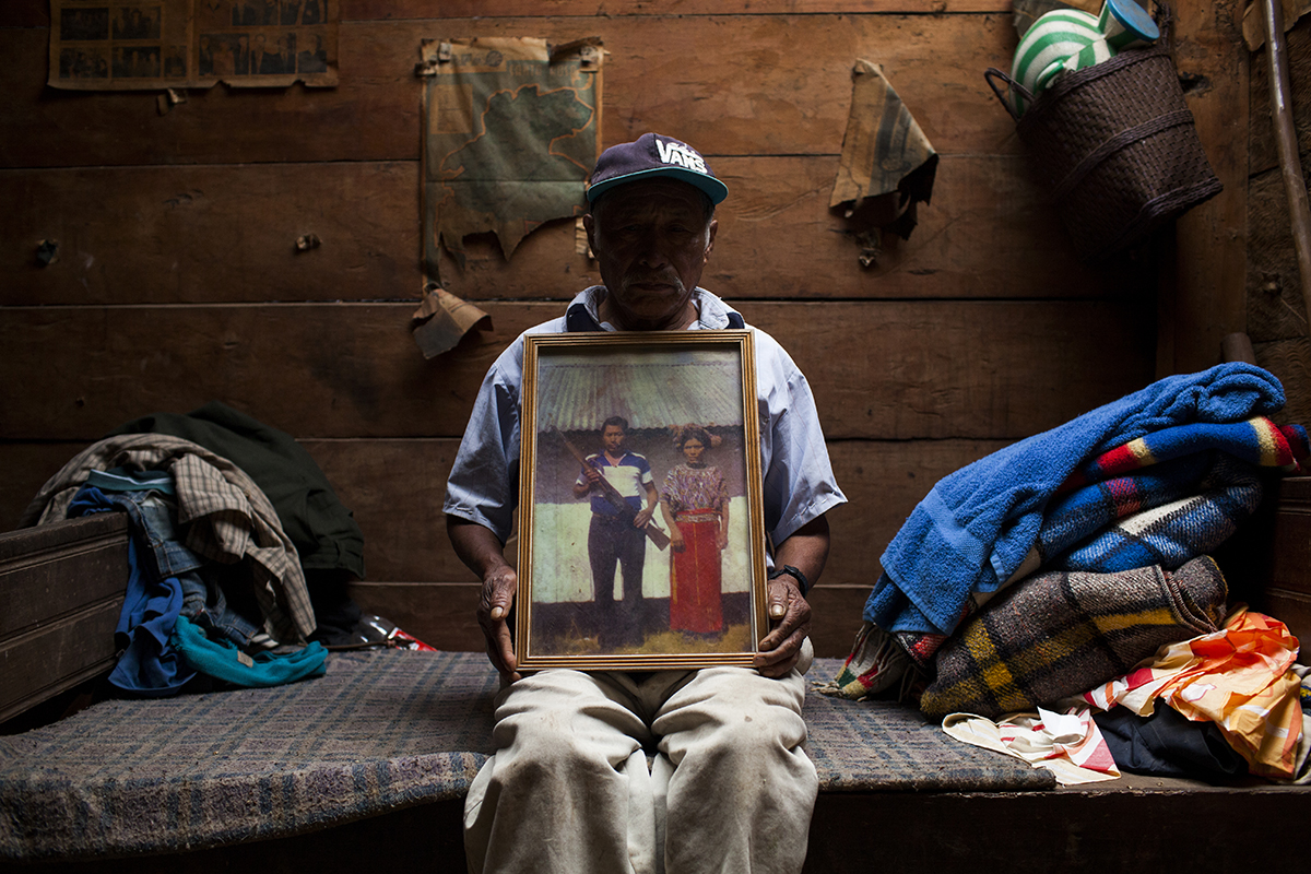 En la casa, el esposo de Feliciana, Pedro Cobo, 72, enseña la foto que lo retrata junto con su esposa. Después de tres años de fuga en la montaña, donde su hijo Diego murió de hambre, la familia entera se entregó al Ejército en Nebaj y don Pedro se volvió miembro de las Patrullas de Autodefensa Civil (PAC)