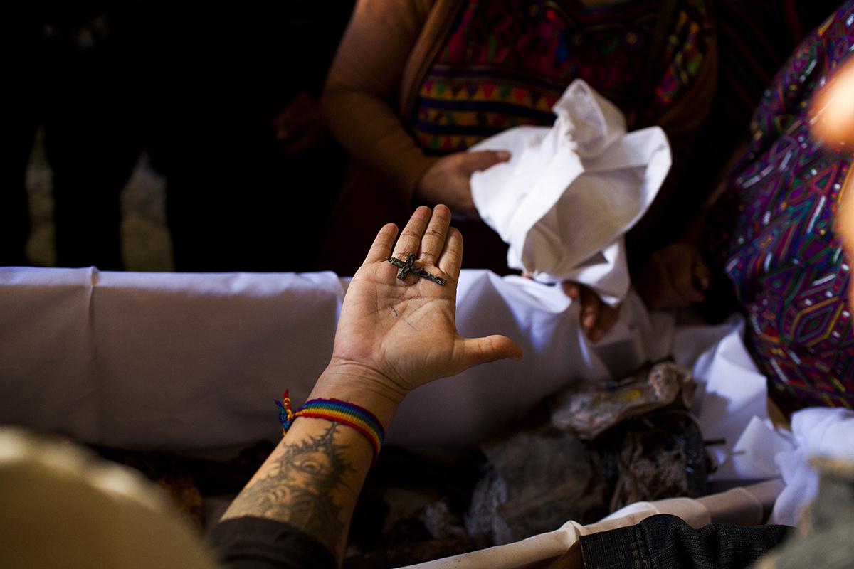 La antropóloga forense Candy Veliz muestra el crucifijo de metal perteneciente a Domingo Solís Bacá, muerto a la edad de 54 años en el 1983.