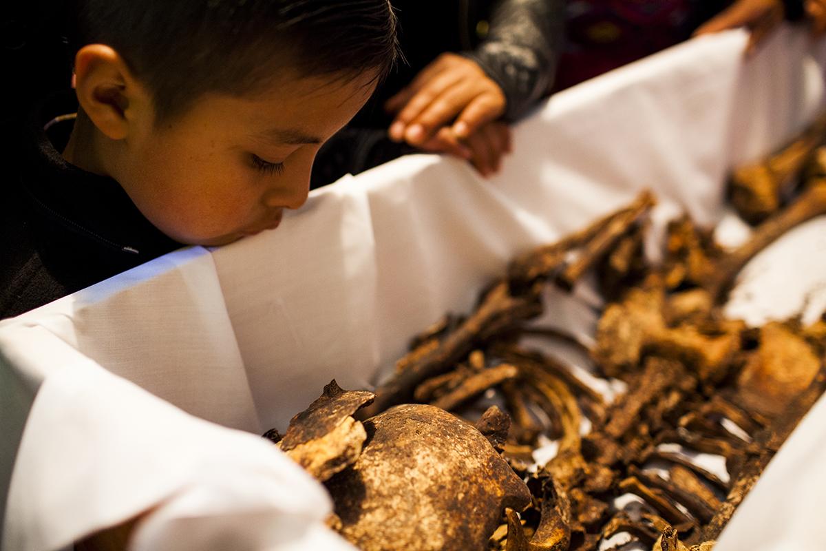 Un niño se asoma al ataúd para mirar los restos de Diego Solís López, muerto a los 72 años en el 1982. Según el relato de los familiares, el anciano fue ejecutado por sus vínculos con la iglesia católica.