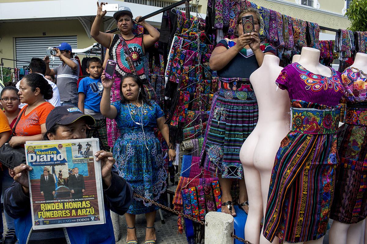 Vendedoras de artesanía típica aprovechan para tomar fotos al féretro presidencial en el Parque Central de la ciudad