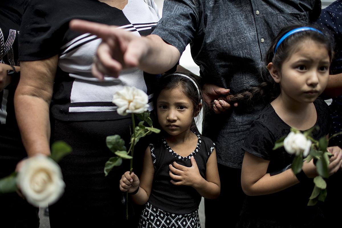 Dos niñas observan el paso del féretro presidencial en la sexta avenida