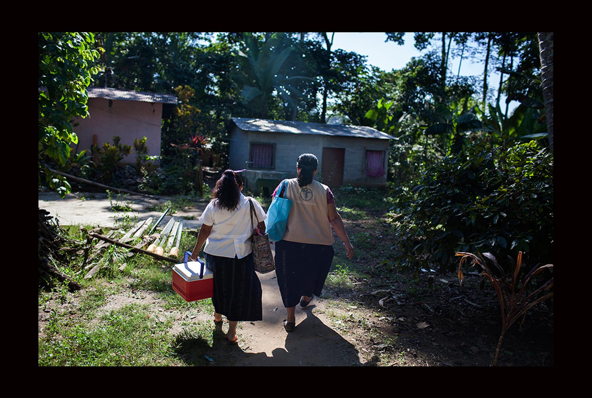 Marta Ofelia Ajpacaja y María Ixquiactap Chop, auxiliares de enfermería, visitan el caserío Xetulul para sacar muestras de agua.