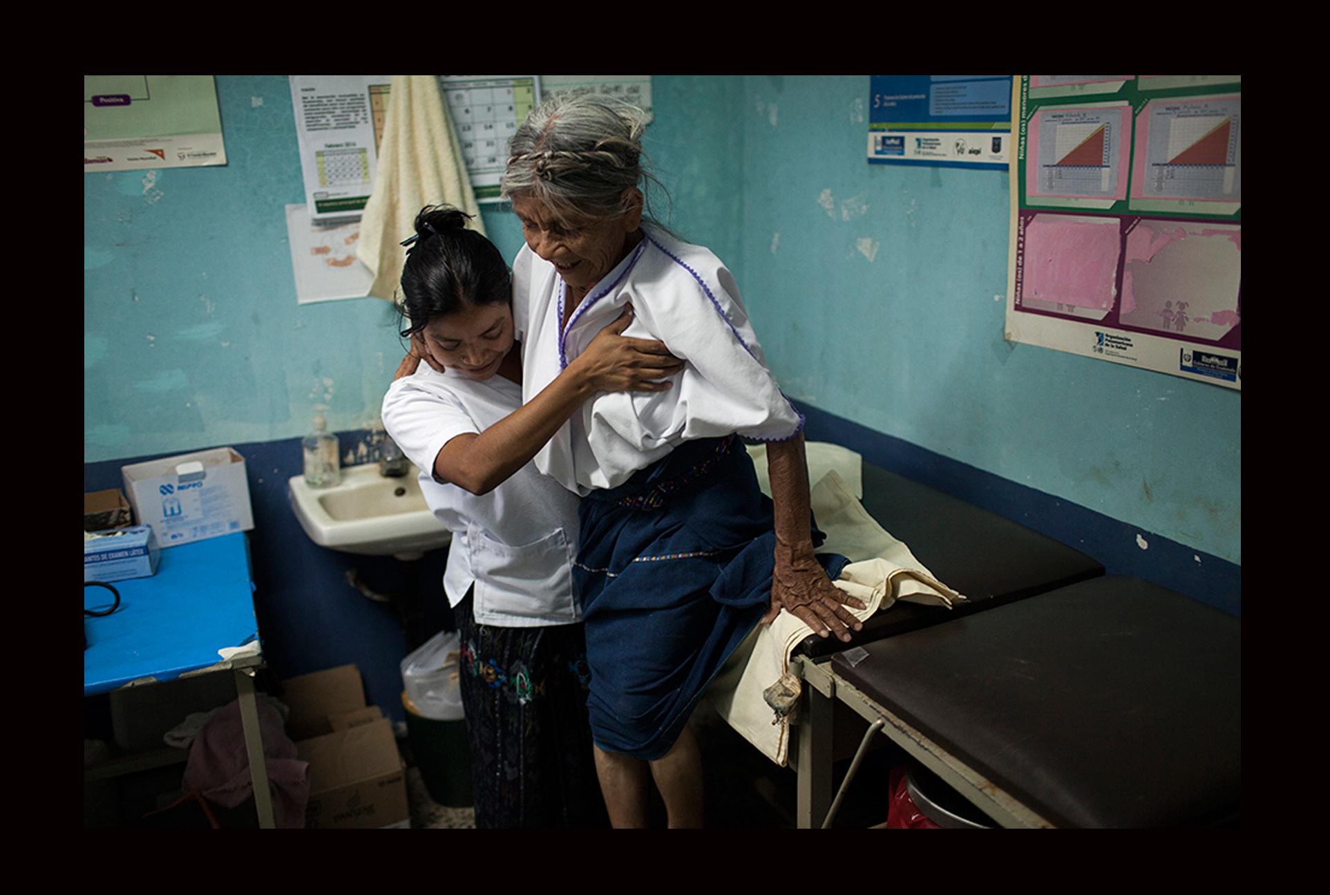 Lucía Sac, de 27 años, ayuda a Santa Cajtunaj, 69, a bajar de la camilla después de haberla examinada.