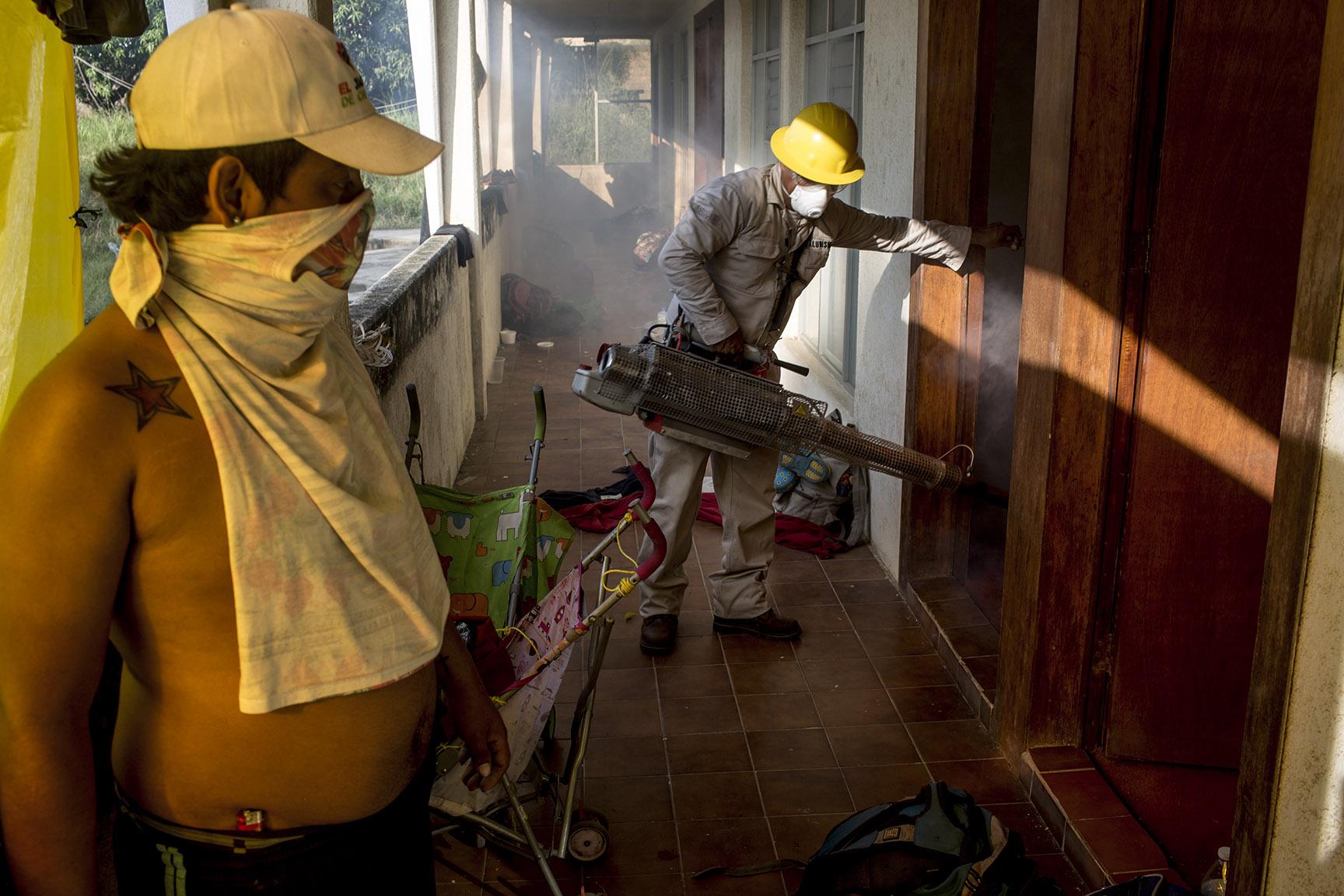 Un empleado municipal fumiga los cuartos del hotel antes de que los migrantes se instalen / Simone Dalmasso