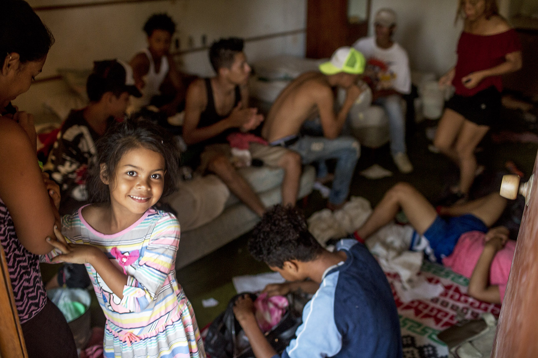 Briany Damas, 6, originaria de San Pedro Sula, sonríe, asomándose del cuarto donde pasó la noche con sus padres y otros 10 migrantes más / Simone Dalmasso