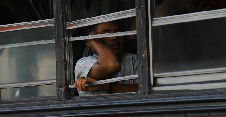 La ventana rota de un bus número 101 sirve de apoyo para un pasajero.