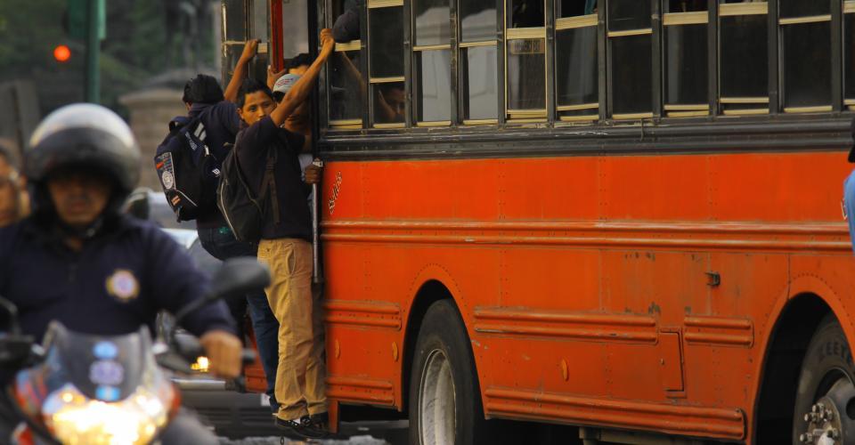 A menudo pasajeros deben colgar fuera del bus.