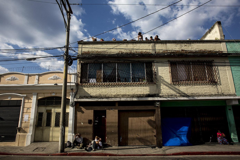 Madre e hijos observan la calle desierta, en la zona 1, justo después de las 16:00 del martes 24, donde sólo quedaban los indigentes que solían pasar la noche en la acera del lugar. Simone Dalmasso