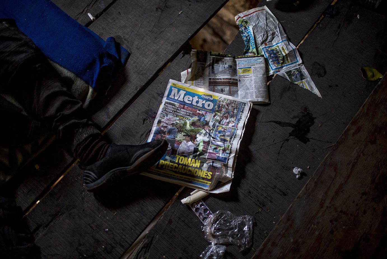 Un vagabundo descansa en el piso de una casa abandonada donde luce el detalle de la portada de un periódico de reciente publicación. Simone Dalmasso