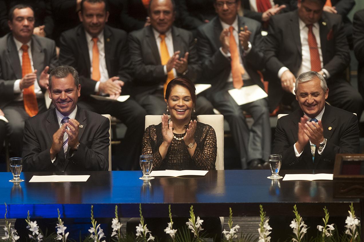 Pérez Molina y Badetti sonríen luego de ser aplaudidos por los diputados y otros asistentes antes de retirarse del teatro.