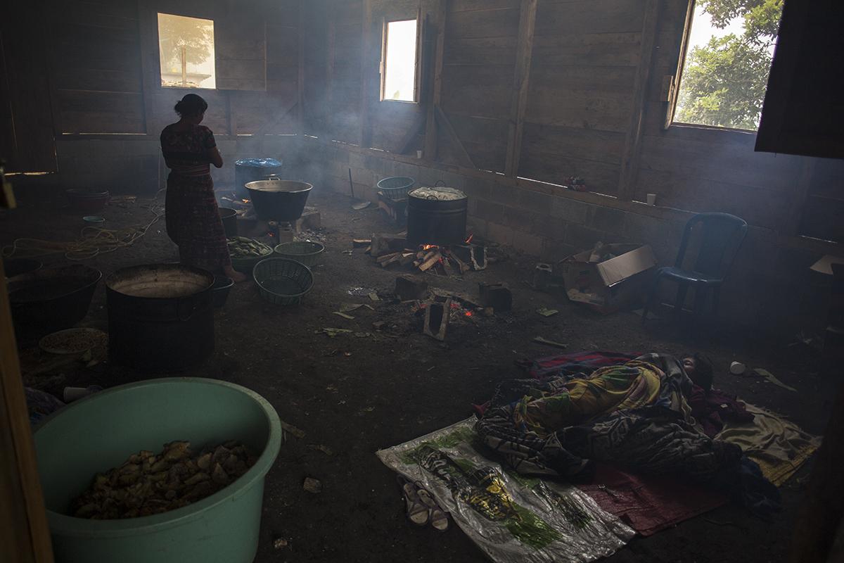 En la madrugada del día del entierro, una cocinera no para con los preparativos del almuerzo, mientras su hija sigue dormida, después del desvelo