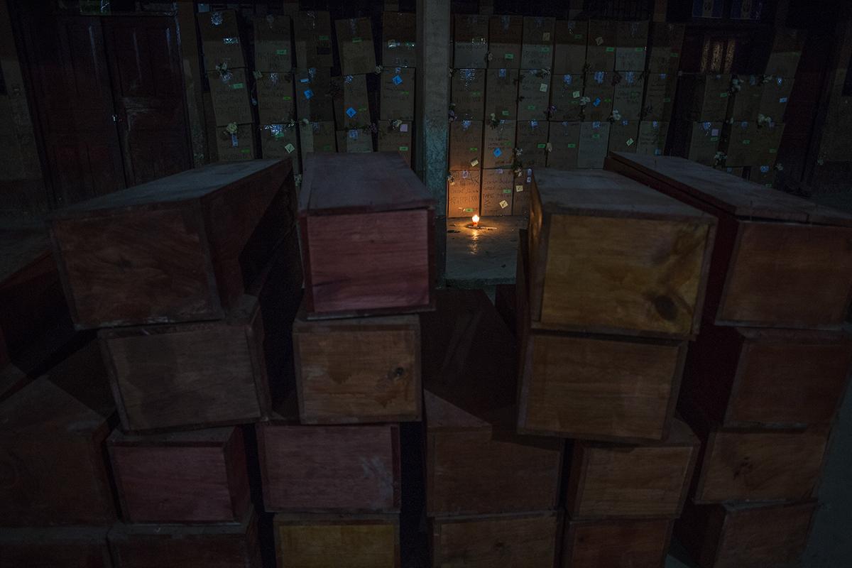 En la noche de los velorios, muchos restos no identificados quedaron en el patio de la escuela, alumbrados por una única vela