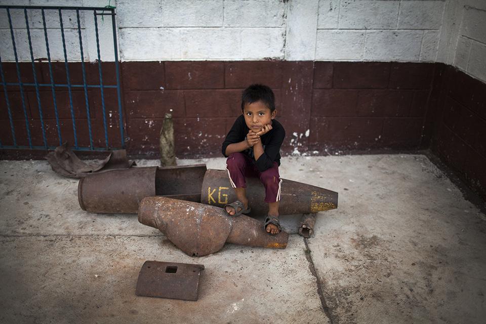 Un niño posa encima de la cáscara de una bomba de 250 Kg que quedó sin estallar durante los bombardeos de los años 80 en Cuarto Pueblo