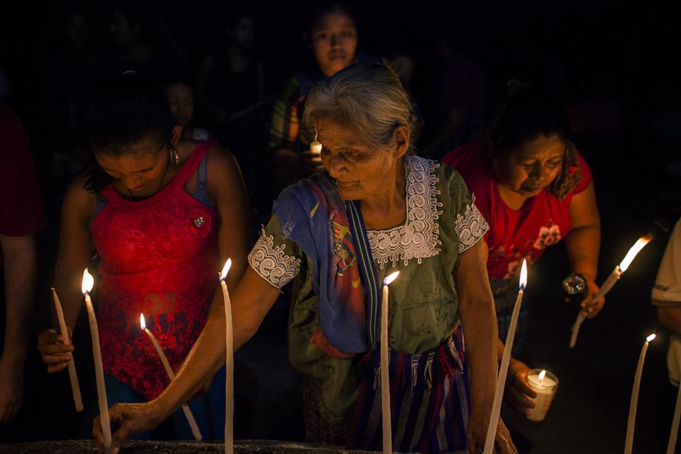 Una anciana enciende unas velas en recuerdo a los familiares caídos en la masacre de Cuarto Pueblo, durante las celebraciones del 34º aniversario del acontecimiento