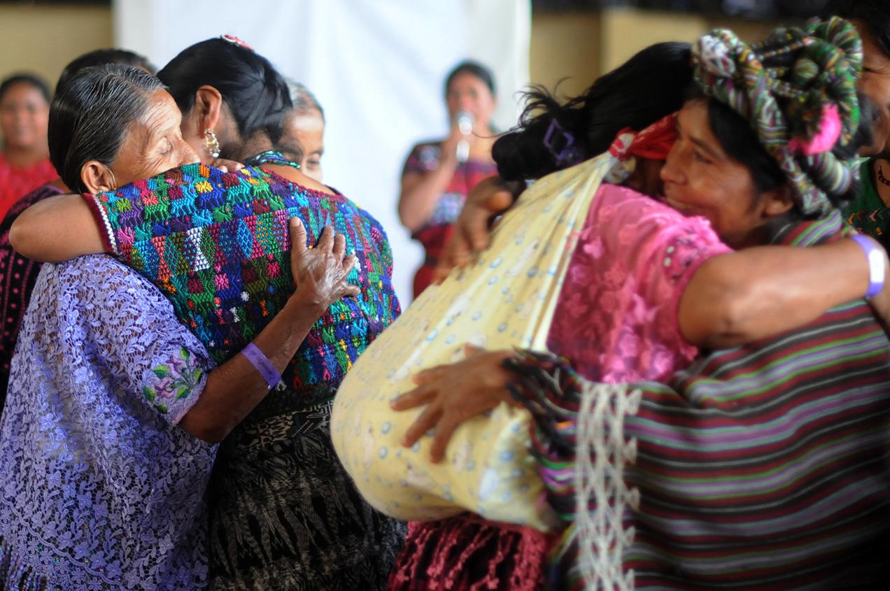 Mujeres ixiles y q'eqchi' se abrazan luego del evento.